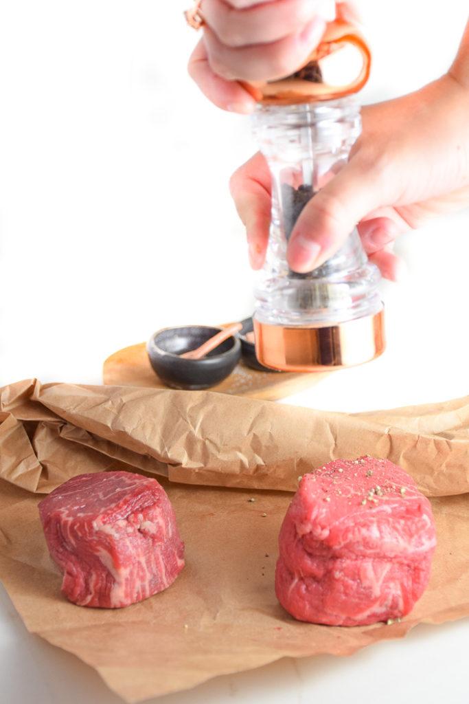 Pepper mill grinding over steak filets